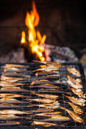 Warm smoked fish in front of fire