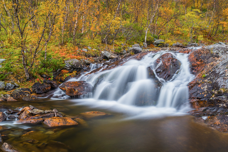 Small waterfall in autumnal landscape Stock Photo