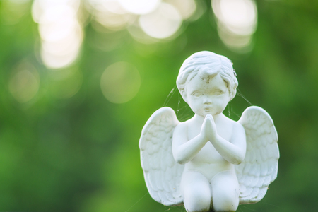 Closeup of small baby angel type memorial object in cemetery