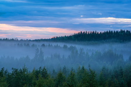Misty summer night extreme terrain landscape and colorful cloudy sky Stock Photo
