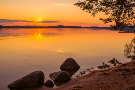 Colorful sunset landscape with water and rocks Stock Photo