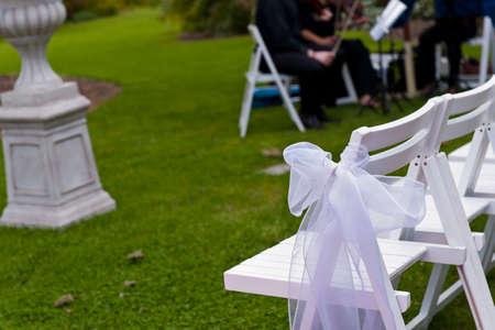 Stühle mit weißen Bändern in einem Outdoor-Garten Hochzeit