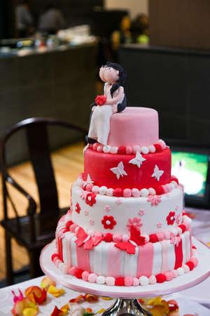 Ein 4-Tier-rosa, rot und weiß schattierte Hochzeitstorte mit Figuren aus dem Paar sitzt an der Spitze mit Blumen.