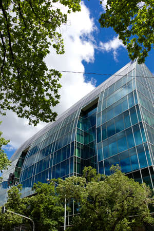 푸른 하늘 아래 나무를 많이으로 둘러싸인 사무실 건물