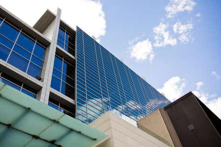 Büroturm von unten reflektiert den blauen Himmel und Wolken angesehen