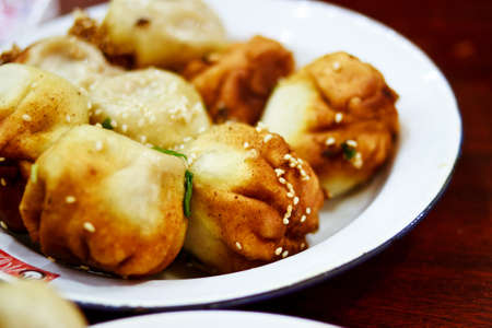 Known as sheng jian bao to the locals, this famous dish is best eaten hot. Stock Photo - 12657370
