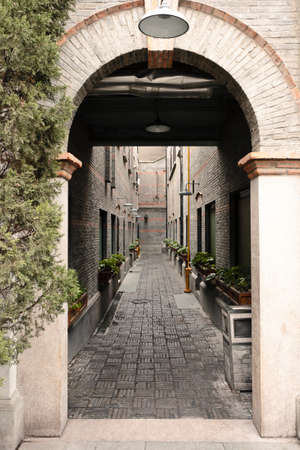 archway: Gazing through the archway lies a narrow alleyway resembling Shanghai of the 30s and 40s