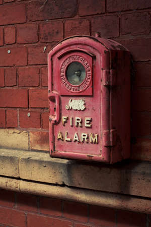 An old fire alarm hanging on the brick wall photo