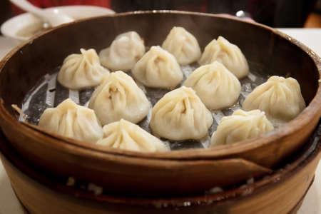 Bekannte den Einheimischen als Xiao Long Bao, was bedeutet, Suppe Knödel, wird es mit einer kreisförmigen Basis und zwickte an der Spitze vor dem dampfenden gemacht Standard-Bild - 12657399