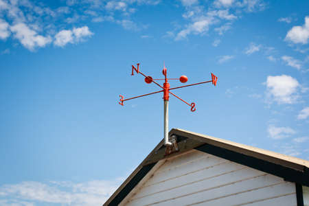red wind vane at the roof top photo