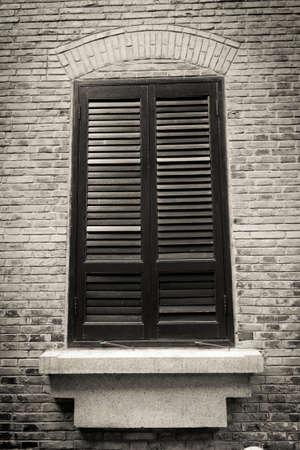 Close up Schuss von einem Holz-Fenster auf der Außenseite eines alten Backsteingebäude in schwarz und weiß