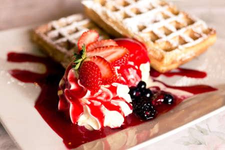 Close up Schuss von Eis mit Erdbeeren und Marmelade auf der Oberseite und belgische Waffeln im Hintergrund
