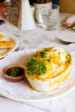 freshly oven baked gourmet chicken shepherd pie served with tomato sauce and green garnish photo
