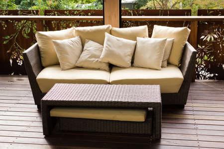 Sofa mit Kissen und eine Menge von Kaffee auf dem Tisch platziert Holzterrasse Editorial