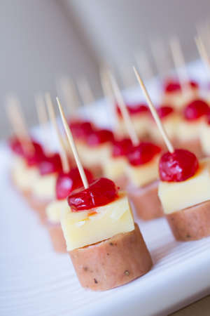 skewed: Appetizers with cherry, cheese and salami skewed on a toothpick placed in a tray