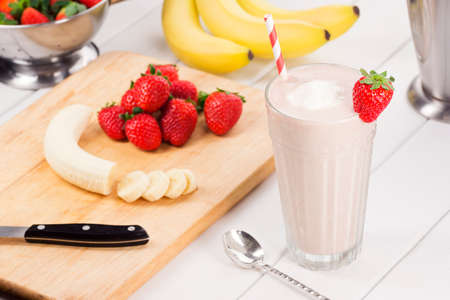 Strawberry and Banana Yogurt Smoothie with Ingredients on White Picnic Table Archivio Fotografico