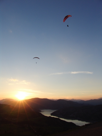 Two paragliders loners are still in the sky in at sunset in Saint Vincent les Forts, France photo