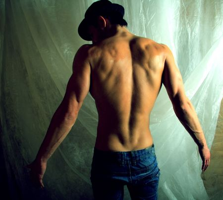undressed young: Brawny guy in hat kind with back. Beauty of human body. Photo.