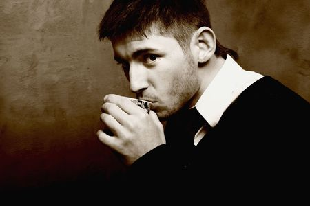 sipping: Beautiful young boy sipping coffee latte. Cepia photo. Stock Photo