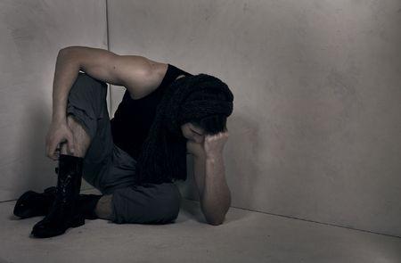 deliberate: desperate prisoner in a grey room. A conceptual art photo.