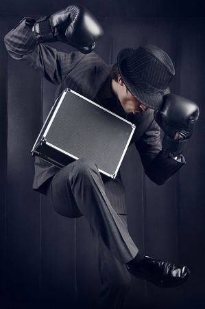 fighting styles: Businessman in boxing gloves with metal suitcase fallen asleep in unusual pose. Photo. Stock Photo