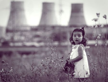 Little girl with a gas mask in hands against power station. Concept: environment and people. photo
