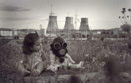 Little girl sitting with a baby doll on gas mask. Concept photo on theme of people and ecology.