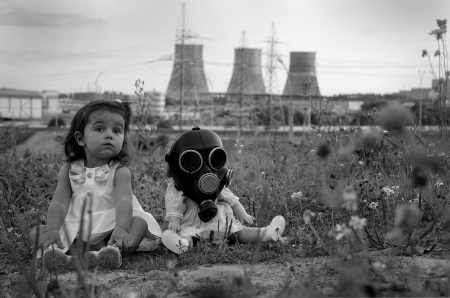 public health: Little girl sitting with a baby doll on gas mask. Concept photo on theme of people and ecology.  Stock Photo