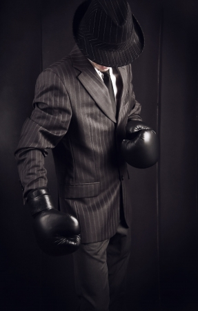 fighting styles: Gangster in grey suit in boxing gloves on his hands. Photo with copyspace.
