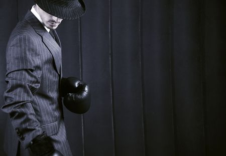 Gangster in grey suit in boxing gloves on his hands. Photo with copyspace.