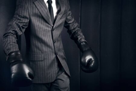 Business person in grey suit and boxing gloves. Conceptual photo with copyspace.