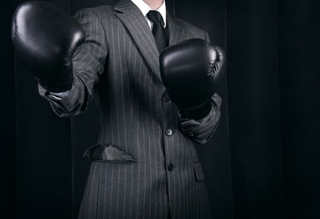 business competition: Business person in grey suit and boxing gloves. Conceptual photo with copyspace.