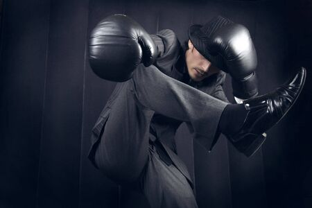 Freakish fighter in a grey suit and grey hat. Conceptual photo with copyspace. photo