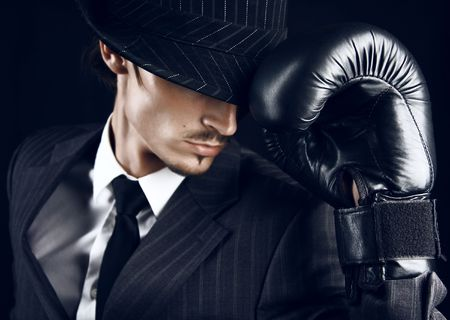 fighting styles: Portrait of stylish gangster in hat dropped on eyes and boxing glove on a hand.
