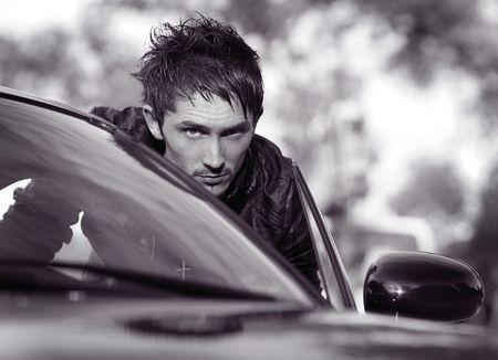 model car: Handsome man standing near the modern sport car. Photo.
