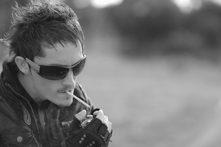 cigarette lighter: sexual smoker in sun glasses. Outdoor portrait. Photo with copyspace.