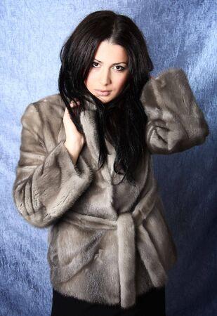 fur coat:  Beautiful brunette woman wearing a fur coat. Photo.