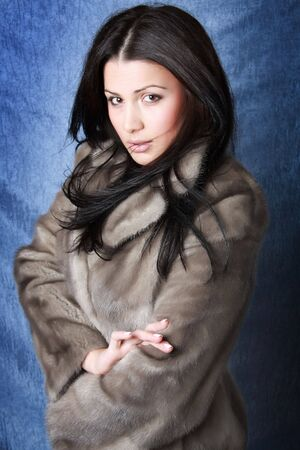 Beautiful brunette woman wearing a fur coat. Photo.