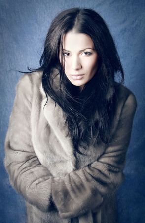 Beautiful brunette woman wearing a fur coat. Photo.  photo