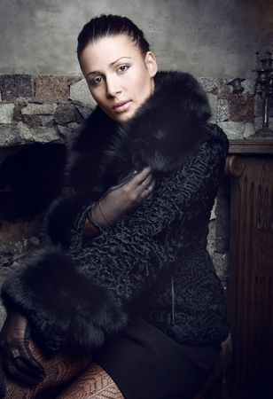 Beautiful brunette woman wearing a fur coat. Photo. Stock Photo