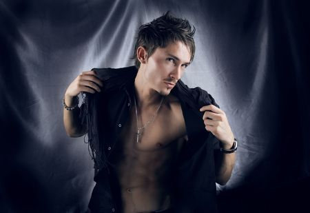 Furious young man with perfect athletic body breaking off shirt on him. Photo. Stock Photo - 5604802