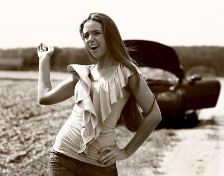 The emotional girl near broken car. Photo.