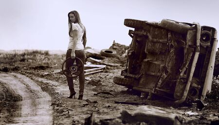 The girl with wheel in a hand against broken car. Photo. photo