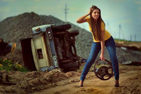 broken car: La chica de la rueda en una mano contra el coche roto. Foto.