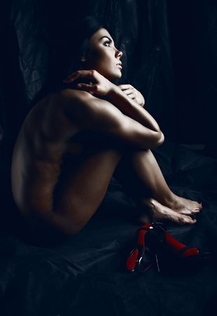 mujer desnuda sentada: j�venes mujeres desnudas sobre fondo negro. Foto.