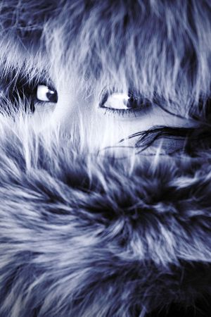young elegant girl hide in fur. Close-up eyes. photo