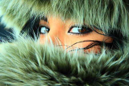 Pretty young woman with a fur hood. Close-up eyes. photo