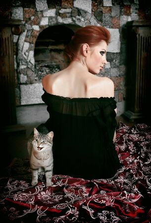 House cat and red-haired girl sitting a back opposite fireplace.  photo