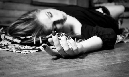 Dead young woman on wooden floor. Studio shot. photo