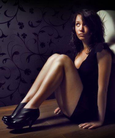 amateur: mujer que llevaba un vestido negro y sentado en el sof� de su sala de estar